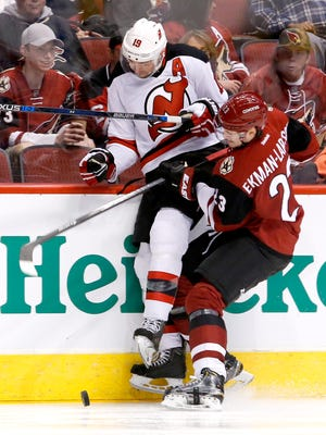 Travis Zajac (19) of the Devils is checked into the boards by Oliver Ekman-Larsson (23) of the Coyotes during the second period of an NHL game at Gila River Arena in Glendale on Saturday, January 16, 2016.