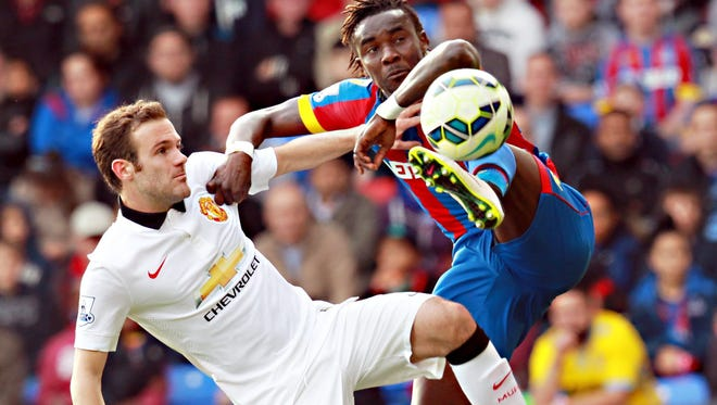 Manchester United's Juan Mata (L) and Crystal Palace's Pape Souare during the English Premier League soccer match between Crystal Palace and Manchester United at Selhurst Park in London.