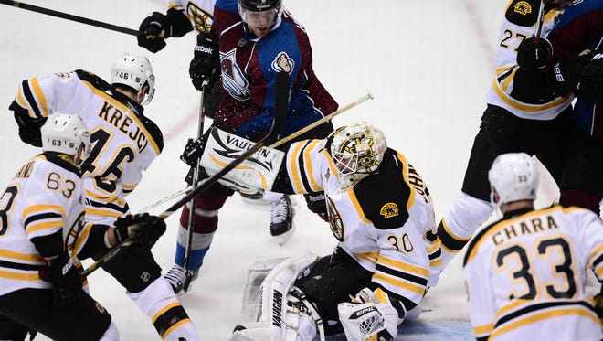 Colorado Avalanche defenseman Jan Hejda (8) attempts against Boston Bruins goalie Chad Johnson (30) in the second period at the Pepsi Center.