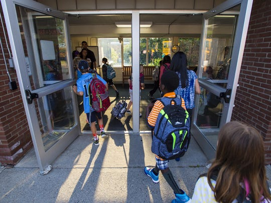 Students stream through the front door on the first day of classes at Orchard School in South Burlington on Tuesday, August 25.