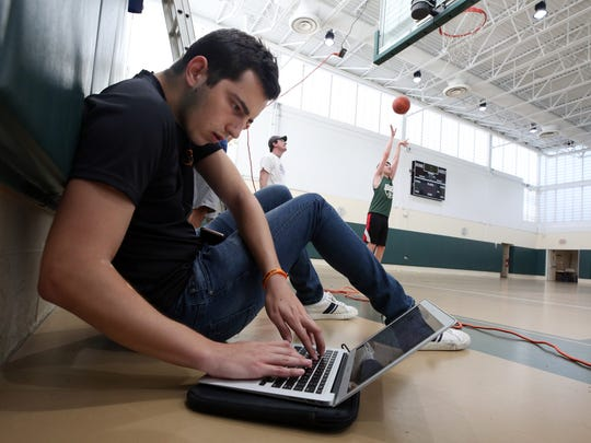 Ben Zirman collects data, as Jesse Gabor shoots baskets, during a demonstration of the RSPCT shooting software in the gym at Solomon Schecter School in Hartsdale Aug. 1, 2018.