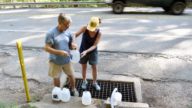 Jeff Smith and Sally Jones fill gallon jugs with fresh spring water from a pipe off Seven Valleys Road Sept. 4, 2016, in North Codorus Township. A pipe installed along the side of Seven Valleys Road between York New Salem and Seven Valleys provides access to a steady stream of spring water, which people have collected free of charge for decades.