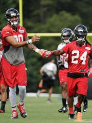 Atlanta Falcons' Levine Toilolo, left, and teammate Devonta Freeman high-five during NFL football training camp July 28, 2016, in Flowery Branch, Ga.