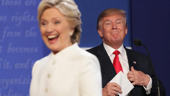 Democratic presidential nominee former Secretary of State Hillary Clinton walks off stage as Republican presidential nominee Donald Trump smiles after the third U.S. presidential debate at the Thomas & Mack Center on October 19, 2016 in Las Vegas, Nevada. (Photo by Chip Somodevilla/Getty Images)