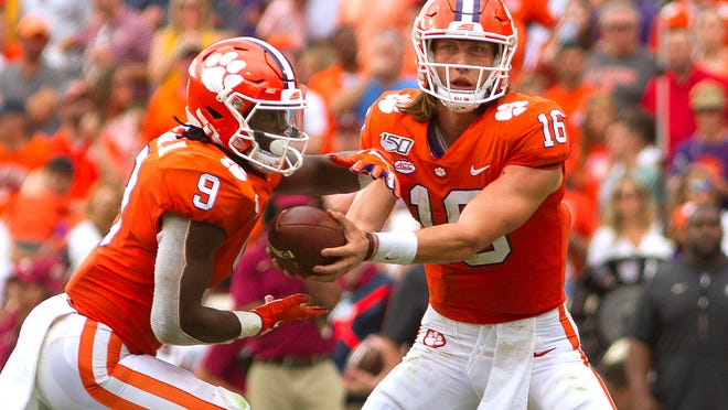 Oct 12, 2019; Clemson, SC, USA; Clemson Tigers running back Travis Etienne (9) takes the ball from quarterback Trevor Lawrence (16) during the first half of the game against the Florida State Seminoles at Clemson Memorial Stadium. Mandatory Credit: Joshua S. Kelly-USA TODAY Sports
