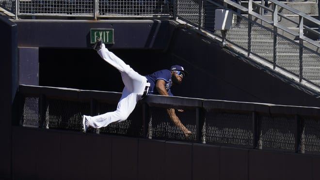 Tampa Bay right fielder Manuel Margot falls over a right field wall after catching a foul ball by Houston center fielder George Springer during the second inning of Monday's game.