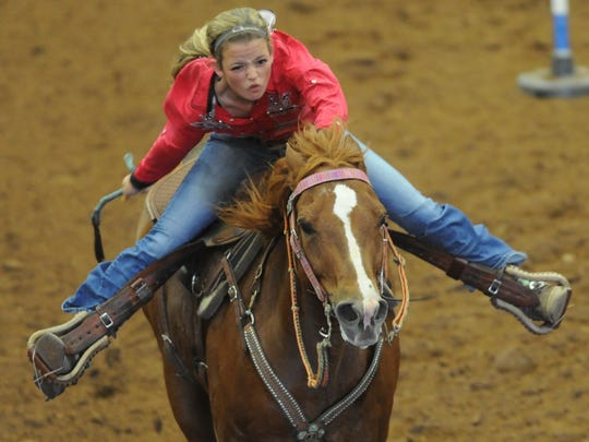 Abilene's Jaxon Schulz and her horse, Showtime, compete in the first pole bending go-around Tuesday, June 6, 2017 during the Texas High School Rodeo Association's State Finals at the Taylor County Coliseum.