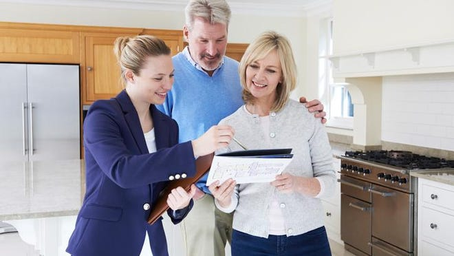 Female Realtor Showing Mature Couple Around New Home