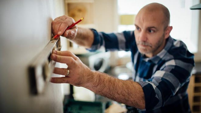 Mature man using a spirit level and marking the wall with a pencil in his kitchen.