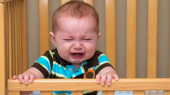 Crying unhappy baby standing in crib