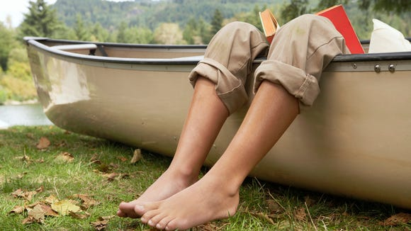 Barefoot boy (9-11 years) reading book in canoe by lake, low section, close-up of legs over edge of canoe