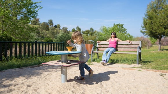 child playing and mother resting in bench
