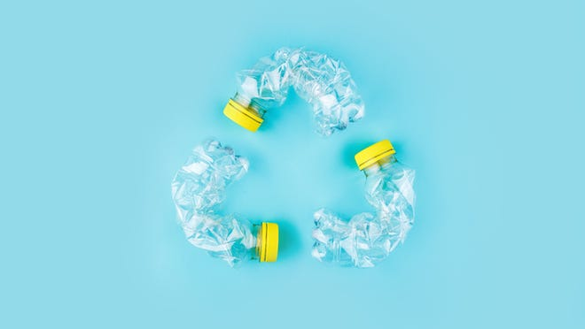 Three bent plastic bottles arranged in the shape of a symbol for recycling