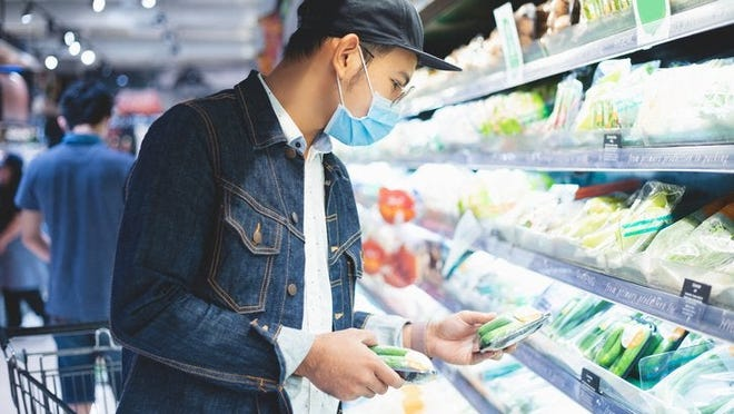 A man wearing a medical mask while selecting produce in a grocery store.