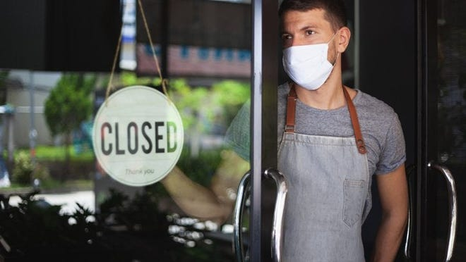 A waiter wearing a medical mask while standing in the doorway of an empty restaurant with a Closed sign hanging on the door.