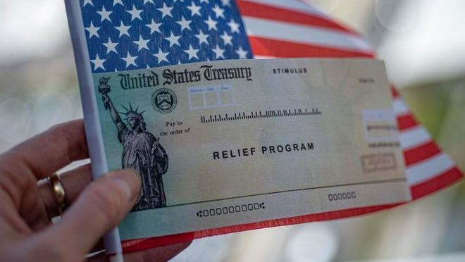 A hand holding a small American flag and a stimulus check from the U.S. Treasury.