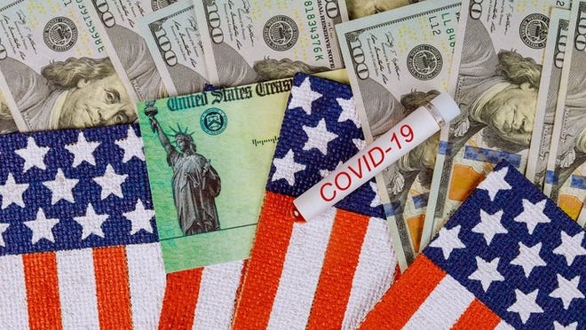 $100 bills, a stimulus check from the U.S. Treasury, and American flags surround a COVID-19 vial.