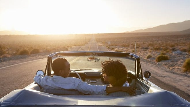 A smiling couple driving their car down an open highway in the desert at dusk.