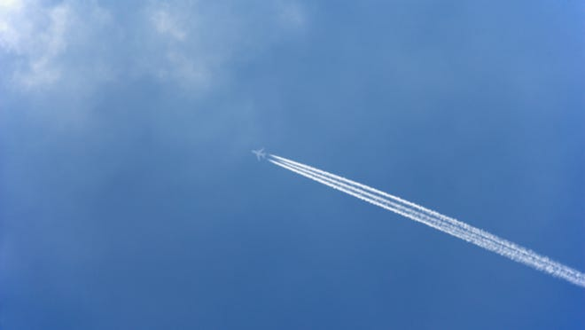 White condensation trail from a commercial airplane as it flies across a blue sky.