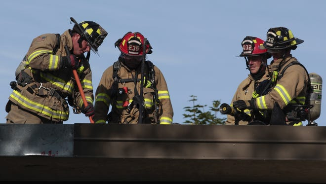 Firefighters use a pike to open up the roof of Shattuck Middle School in order to place a hose in it on Thursday, July 6, 2016 in Neenah, Wis.