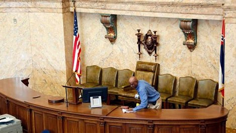 House porter Leroy Walker Jr., puts a final polish on the Speaker's podium in the House chambers at the Capitol in Jackson, Miss., Monday Jan. 5, 2015. House and Senate staff are tending to last minute details at the Capitol as Mississippi lawmakers begin their three-month session at noon Tuesday, and they'll be greeted by diverse groups trying to influence public policy. (AP Photo/Rogelio V. Solis)