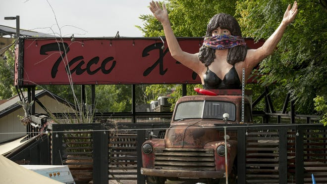 The famous statue of Maria Corbalan wears a mask at Maria's Taco Xpress on South Lamar Boulevard in July.
