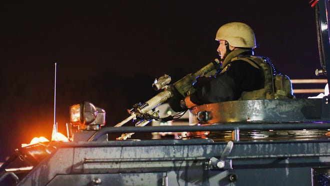 Police confront demonstrators Friday during a protest over the shooting death of Michael Brown in Ferguson, Missouri. Police shot pepper spray,  smoke, gas and flash grenades at protestors before retreating.