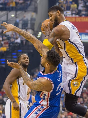 Indiana Pacers forward Paul George (13) pulls down a rebound over Philadelphia 76ers forward Shawn Long (36) in the first half of the game at Bankers Life Fieldhouse on  Sunday, March 26, 2017.