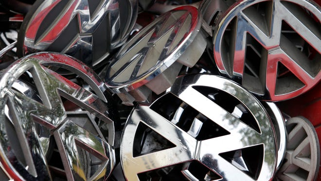 In this Sept. 23, 2015 file photo Volkswagen ornaments sit in a box in a scrap yard in Berlin, Germany.