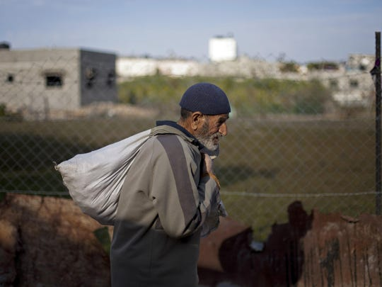 A Palestinian man carries a sack of food as he walks in the Jabalya refugee camp in the northern Gaza Strip. Tens of thousands of Palestinians are no longer getting food aid or health services from America after the Trump administration's decision in 2018 to cut more than $200 million in aid to the Palestinians.