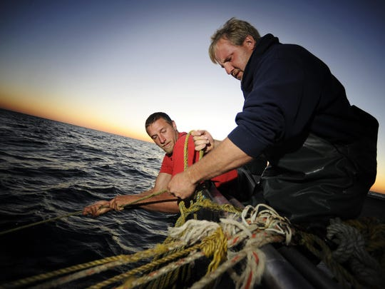 Jeremy Kulpa, right, and Kevin Schnell, both of Two Rivers, pull in ropes attached to a trap net during a commercial fishing trip on Lake Michigan for the Susie Q Fish Co. in Two Rivers.