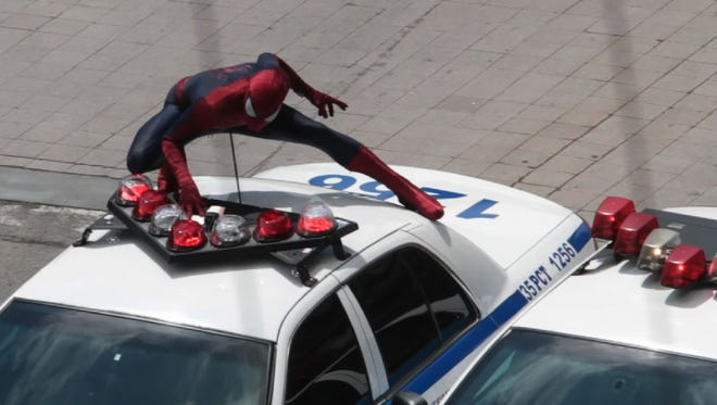 Spiderman rides on top a NYC Police car on Main Street heading west in downtown Rochester on May 9, 2013.