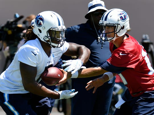 Titans quarterback Matt Cassel, right, hands the ball off to running back Derrick Henry during practice June 9.