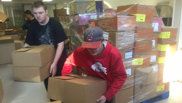 Kylor Britton, left, and Michael Imboden move boxes for the mobile food pantry.