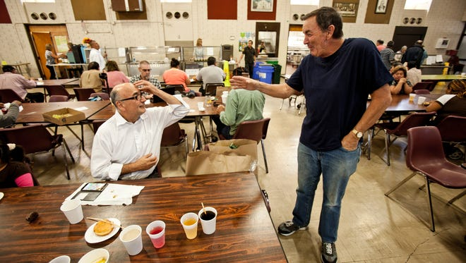 Catholic worker Larry Purcell, right, talks to Bill Prada at St. Anthony's Padua Dining Room in Menlo Park, Calif., on Oct. 29.