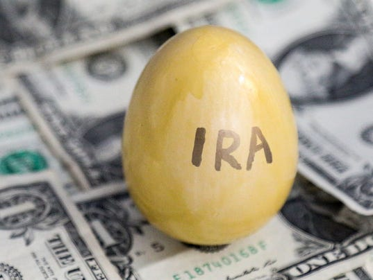 Golden eggs marked IRA on a background of dollars