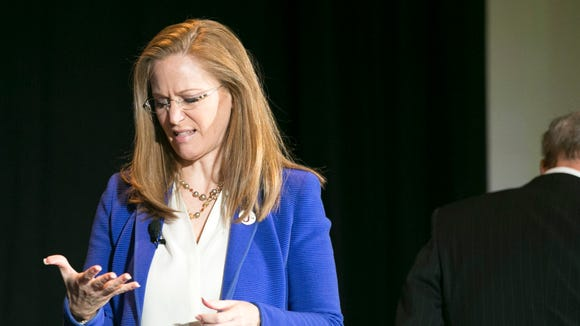 Business woman Christine Jones,  gubernatorial candidate for Arizona looks at the palm of her hand after shaking hands with former U.S. Congressman Frank Riggs, a gubernatorial candidate for Arizona, while taking the stage for a forum for Arizona gubernatorial candidates hosted by the Arizona Republic and The Arizona We Want Institute at the Phoenix Convention Center on Friday, June 6, 2014.