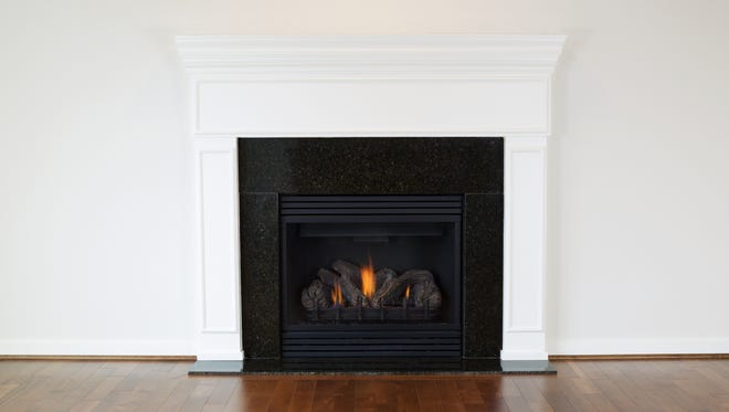 Natural gas fireplace with a white mantle and cherry wood floors