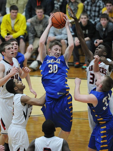 Michael Bruns pulls down a rebound for Carmel. in a semi-final game of the Noblesville sectional Friday March 7, 2014