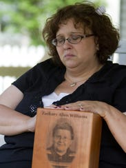 Tammy Niederhelman holds an urn May 8, 2012, with the