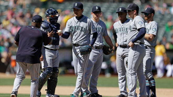 Seattle Mariners pitcher Hisashi Iwakuma, third from left, hands the ball to manager Lloyd McClendon, left, as he is removed in the seventh inning of a baseball game against the Oakland Athletics, Sunday, Sept. 6, 2015, in Oakland, Calif.