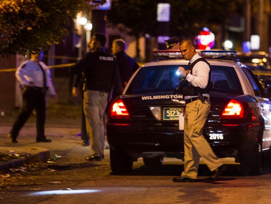 An officer investigates the scene of a shooting on