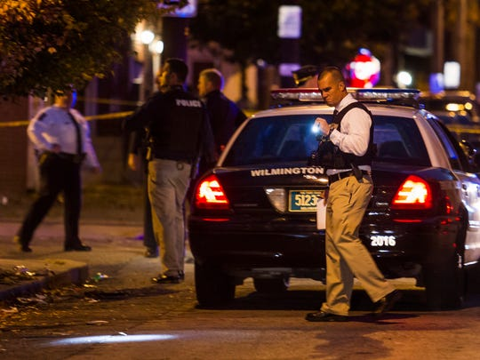 An officer investigates the scene of a shooting on Taylor Street in Wilmington.