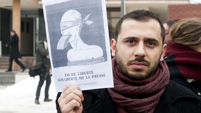 "A Kosovar journalist holds a sign reading in French, ""No freedom without the freedom of the press"" as people gathered on the streets of Pristina on Jan. 8, 2015."