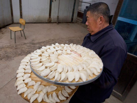 A man collects dumplings to store ahead of the Chinese lunar new year at a village on the outskirts of Beijing, China, Thursday, Jan. 26, 2017.