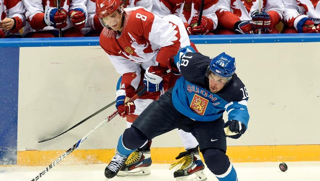 Finland defenseman Sami Lepisto (18) battles for the puck with Russia forward Alex Ovechkin (8) on Wednesday.