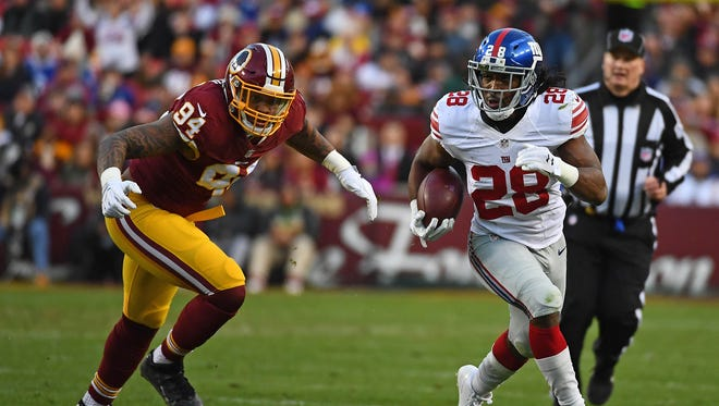 New York Giants running back Paul Perkins (28) rushes the ball as Washington Redskins linebacker Preston Smith (94) looks on during the first half at FedEx Field.