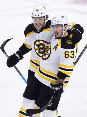 In this Tuesday, Oct. 23, 2018, file photo, Boston Bruins right wing David Pastrnak (88) celebrates a goal with teammate Brad Marchand (63) against the Ottawa Senators during the third period of an NHL hockey game, in Ottawa, Ontario. The Boston Bruins could be without two thirds of their top line when the next NHL season starts after David Pastrnak and Brad Marchand each underwent surgery in September 2020.