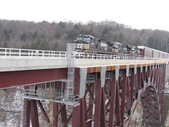 A train crosses the new railroad bridge over the Genesee