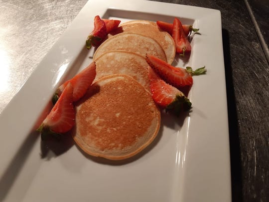 Lemai pancakes with a side of strawberries are displayed.